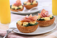 Breakfast. Baked bun with cheese, spinach, prosciutto and orange juice