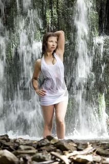 Junge Frau posiert im Wasserfall