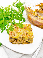 Casserole of meat and eggplant in plate on napkin