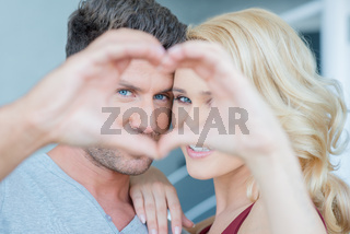 Couple Looking Through Hands Making Heart Shape