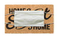 Welcome Mat With Medical Face Mask Amidst The Coronavirus Pandemic Isolated on White