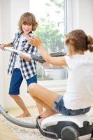 Zwei Kinder spielen mit Staubsauger