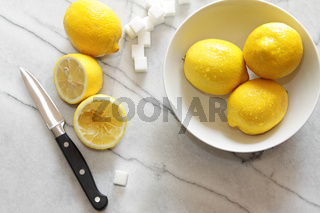 Fresh lemons and sugar cubes on marble counter