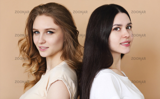 Two beautiful multicultural young women over beige background