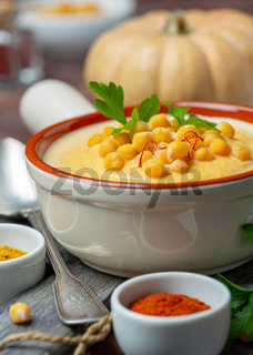 Spicy cream soup of chickpeas and pumpkin close up.