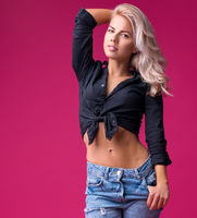 Woman in top and jeans against pink background