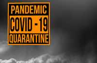 Pandemic sign warning of quarantine due to Covid-19 or corona virus against dark storm clouds