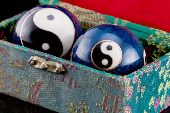 Two blue Qigong balls with white yin and yang symbols in green box