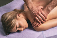 Male masseur doing massage on beautiful naked woman body in the spa salon. Beauty treatment concept.