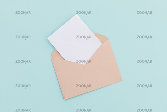 Opened brown envelope with white letter lying over pale blue background
