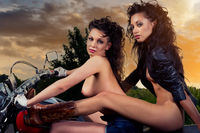 Two sexy naked women sitting on a motorcycle outdoors