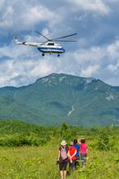 Group of women travelers watching flight of tourist helicopter in sky on background mountains, green forest, clouds in summer sunny weather