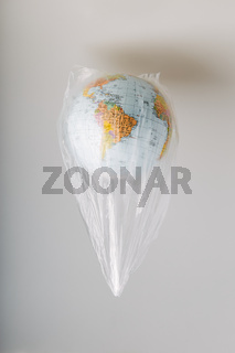 Globe in a plastic bag. Earth contaminated by plastic waste