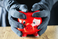 Hands in gloves enclose a piggy bank