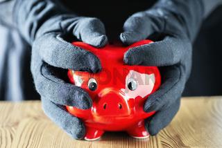 Hände in Handschuhen umfassen ein Sparschwein