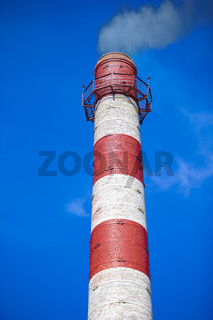 Vertical factory chimney with smoke