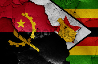 flags of Angola and Zimbabwe painted on cracked wall