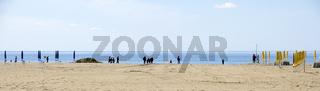 Sandiger Badestrand mit am Ufer spazierenden Menschen in Grado