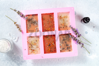 The process of making handmade soap. Glycerin with herbs, poured into a special mold for drying