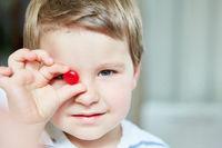 Junge hält einen roten Bonbon in einer Hand