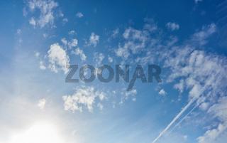 Blauer Himmel mit Wolken und Sonne am Tag
