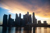 Singapur, Republik Singapur, Blick ueber Marina Bay auf das Geschaeftsviertel mit Wolkenkratzern im Abendlicht