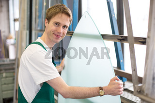 Worker in glazier's workshop handling glass