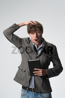Young brown haired surprised man smiling touching head gesture on camera isolated on white background. Wow expression.