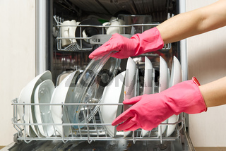 Dirty dish in open integrated dishwasher. Open dishwasher with dirty dishes inside before washing. full loaded dishwasher ready for washing.