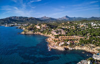 Aerial panorama of Costa de la Calma shoreline and turquoise clear green water of Mediterranean Sea. Hillside villas between pine forests, mountain range in valley. Mallorca, Majorca, Balearic Spain
