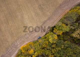 Aerial view from a drone above dirt road across the agricultural field and forest area.