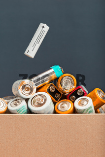Used battery falling into a cardboard box filled with discharged batteries