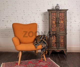 French orange wingback armchair, decorated cupboard, on white bricks wall and grunge wooden parquet