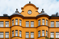 Traditional residential house in Stockholm. Yellow painted facade against sky