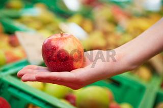 Apfel auf Hand im Supermarkt