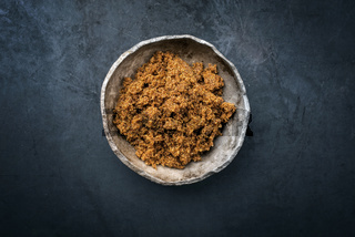 Traditional brown muscovado sugar offered as top view in a rustic earthenware dish with copy space