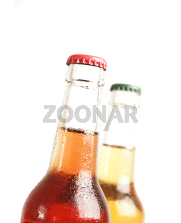 Two ice-cold bottles with organic lemonade against a white background