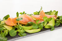 Salmon, avocado and green salad on black tray.