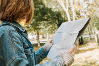 Lifestyle portrait of young adult female in a forest or park holding map in her hands, selective focus