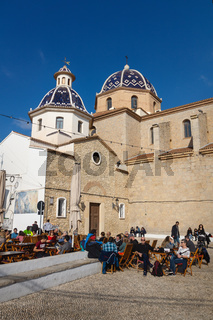 Visitors on restaurant terrace in front of blue domed church of Altea old town square, Spain