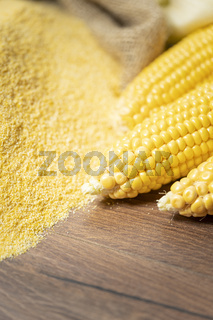 Ripe young sweet corn cob and cornmeal on background close up