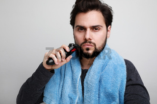 Close-up of bearded man shaving his beard in bathroom, holding shaver machine. Space for text.