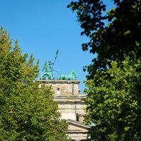 Quadriga at the Brandenburg Gate in Berlin seen through a gap between street trees