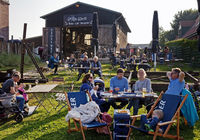 People in the beer garden of the Alte Werft at the historic harbor, Toenning, Germany, Europe