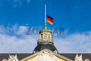 Close view on German Flag at Halfmast, auf Halbmast, on the tower roof of Castle Karlsruhe. Baden-Württemberg, Germany