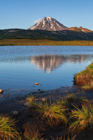 Autumn volcanic landscape, evening view of volcano and reflection of mountains peak in alpine lake