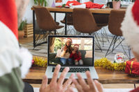Rear view of man and son in santa hats waving while having a videocall with woman and daughter in sa