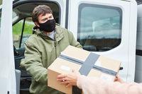 Lieferdienst übergibt Paket an Kundin vor Transporter