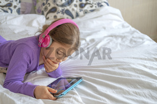 Girl in pink headphones with tablet device