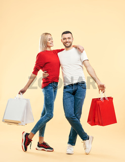 Full length portrait of young happy couple with shopping bags in hands posing over beige background